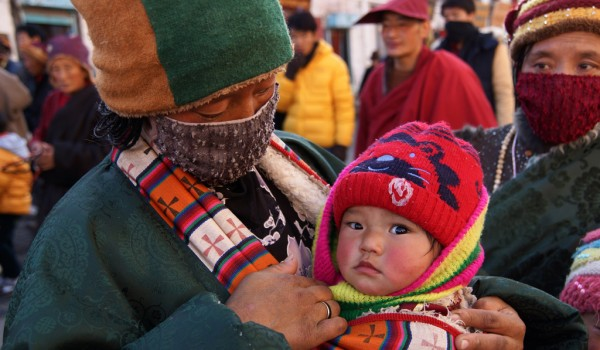 Lhasa: a young woman with her baby at Barkhor Street