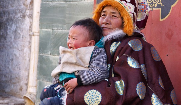 Lhasa: a resting woman with her grandchild at Barkhor Street
