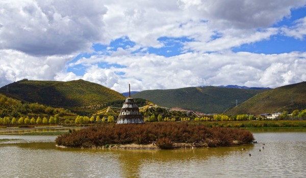 Stupa with mani stones in the lake in front of the Ganden Sumtseling Monastery near Shangri La (Zhongdian), Yunnan