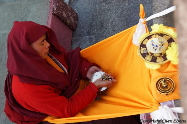 Lhasa: pilgrim in front of the Jokhang Temple doing mandala offering
