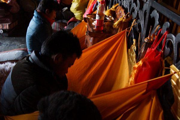 Lhasa: pilgrims inside of the Jokhang Temple doing mandala offering