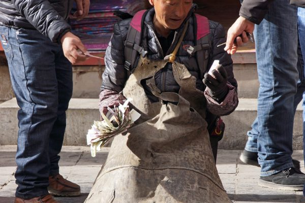 Lhasa: prostrating pilgrim at the Barkhor and receiving some money from passersby