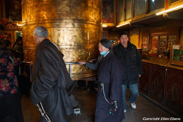 Lhasa: turning the big prayer wheel in a small chapel at the Barkhor