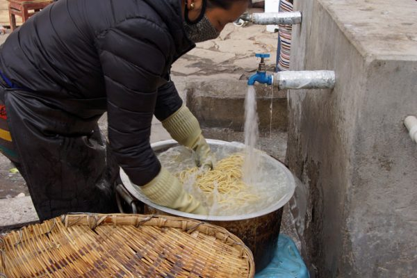 Lhasa: washing noodles in front of Meru Nyignba Monastery (situated behind the Jokhang Temple)