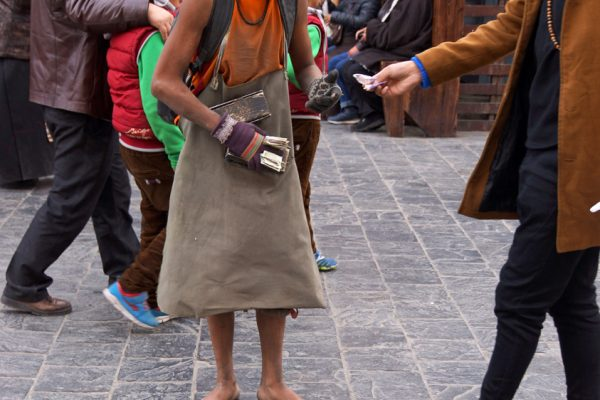 Lhasa: prostrating young pilgrim at the Barkhor and receiving some money from a passersby