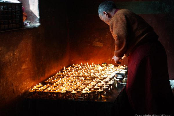 Lhasa: monk lighting candles at Pabongka Monastery