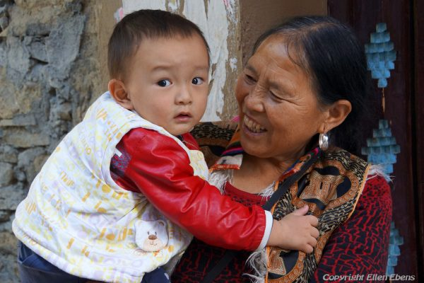 Woman with young child at the village of Ganpucun (Lixian Ganbaozangzhai Scenic Area)