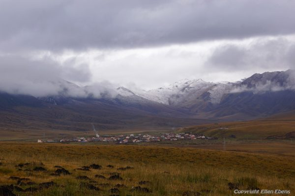 Driving from Zoige to Xiahe with fresh snow on the mountains with in front the village of Heila