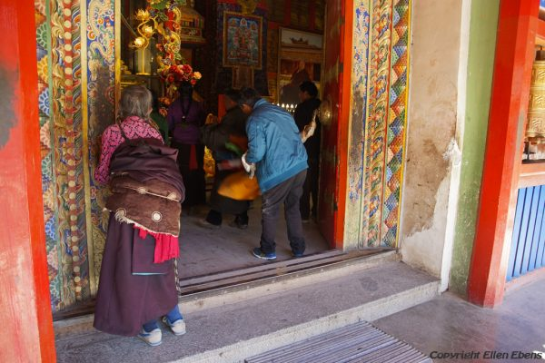 Pilgrims enter the big guilded stupa of Labang Monastery, Xiahe