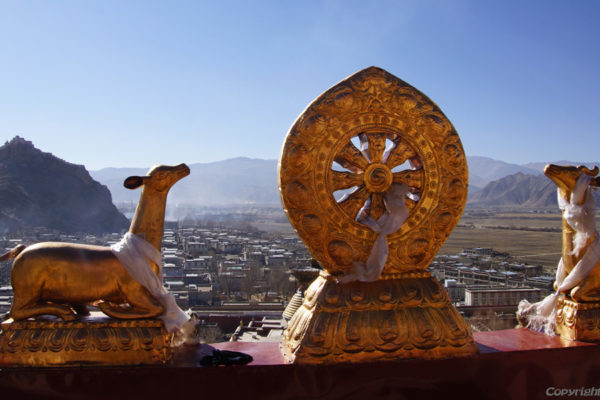The Tibetan Buddhist symbols of the dharma wheel and deer sculptures on the upper hall at the Pelkor Chöde Monastery