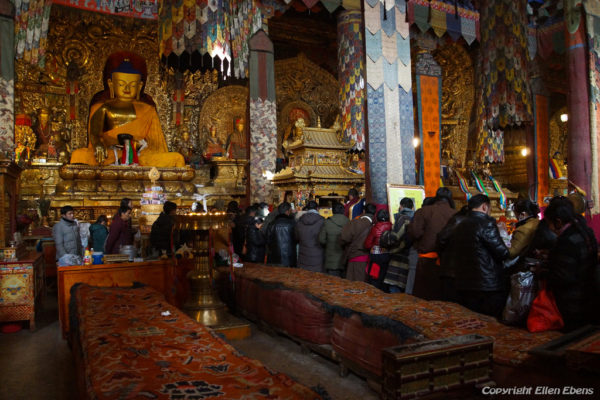 Pilgrims inside the main assembly hall of Sakya Monastery and waiting for a blessing