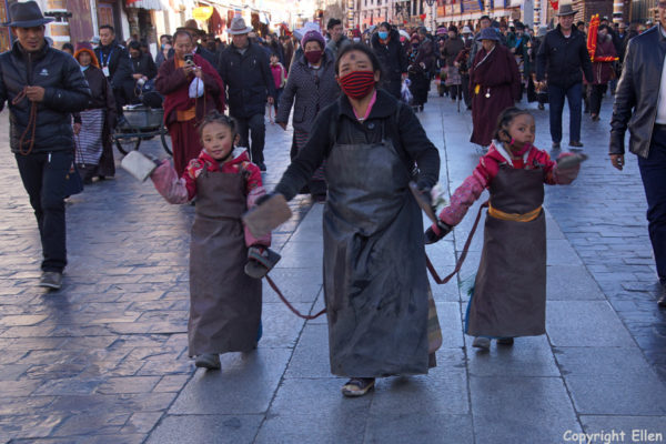 Prostrating mother with her two daughters at the Barkhor around the Jokhang Temple, Lhasa