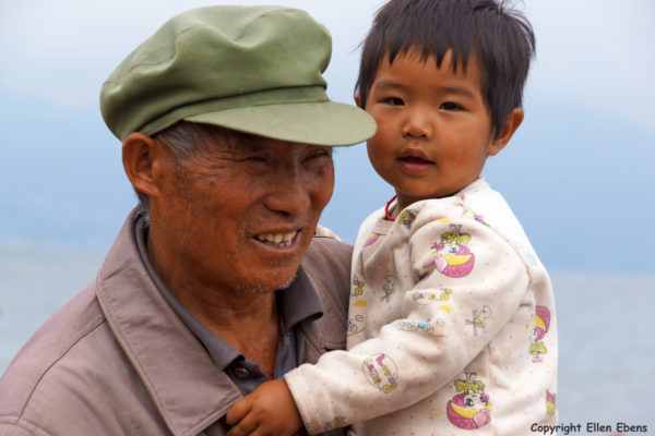 Grandfather with grandchild at Fuxian Lake