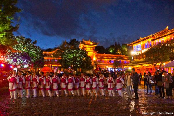 The ancient city of Lijiang. Naxi women dancing at the big square.