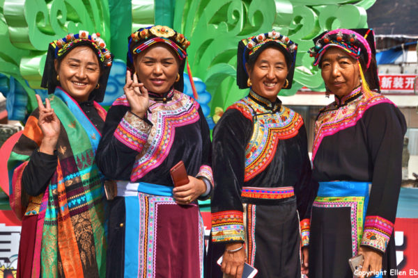 Women wearing beautiful traditional clothes on the wall of the ancient town of Songpan