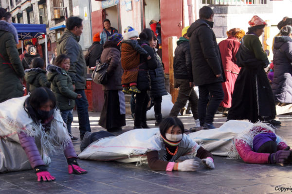 Lhasa, Barkhor Street. Pilgrims prostrating around the holy Jokhang Temple.