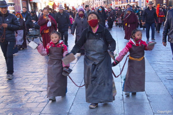 Lhasa, Barkhor Street. A mother and her two young daughters prostrating around the holy Jokhang Temple.