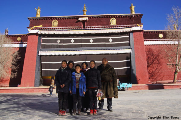 Tibetan family posing in front of the Main Assembly Hall of Pelkor Chode Monastery