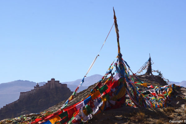 The Gyantse Dzong with prayer flags on the foreground