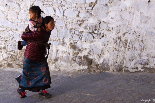 Pilgrim with young daughter climbing up to the chapels of Tashilhunpo Monastery, Shigatse