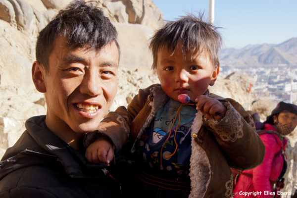 Father with his young son walking the kora around Tashilhunpo Monastery, Shigatse