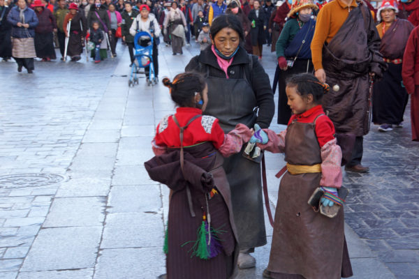 Lhasa, mother with her two young daughters prostrating around the Jokhang Temple
