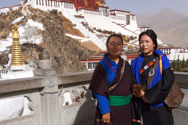 Lhasa, two Tibetan women posing with the Potala Palace
