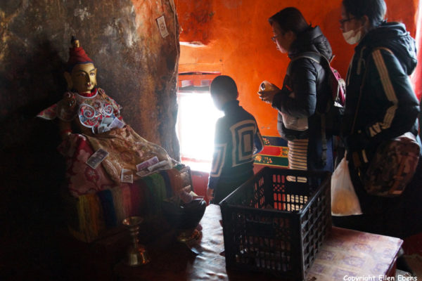 Pilgrims with the statue of King Songtsen Gampo inside one of the caves at Drak Yerpa Meditation Caves
